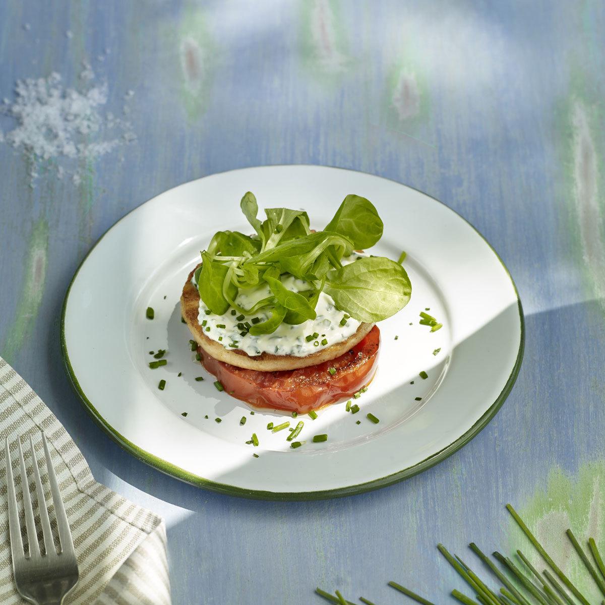 Hamburguesa de trucha con tomate a la parrila.