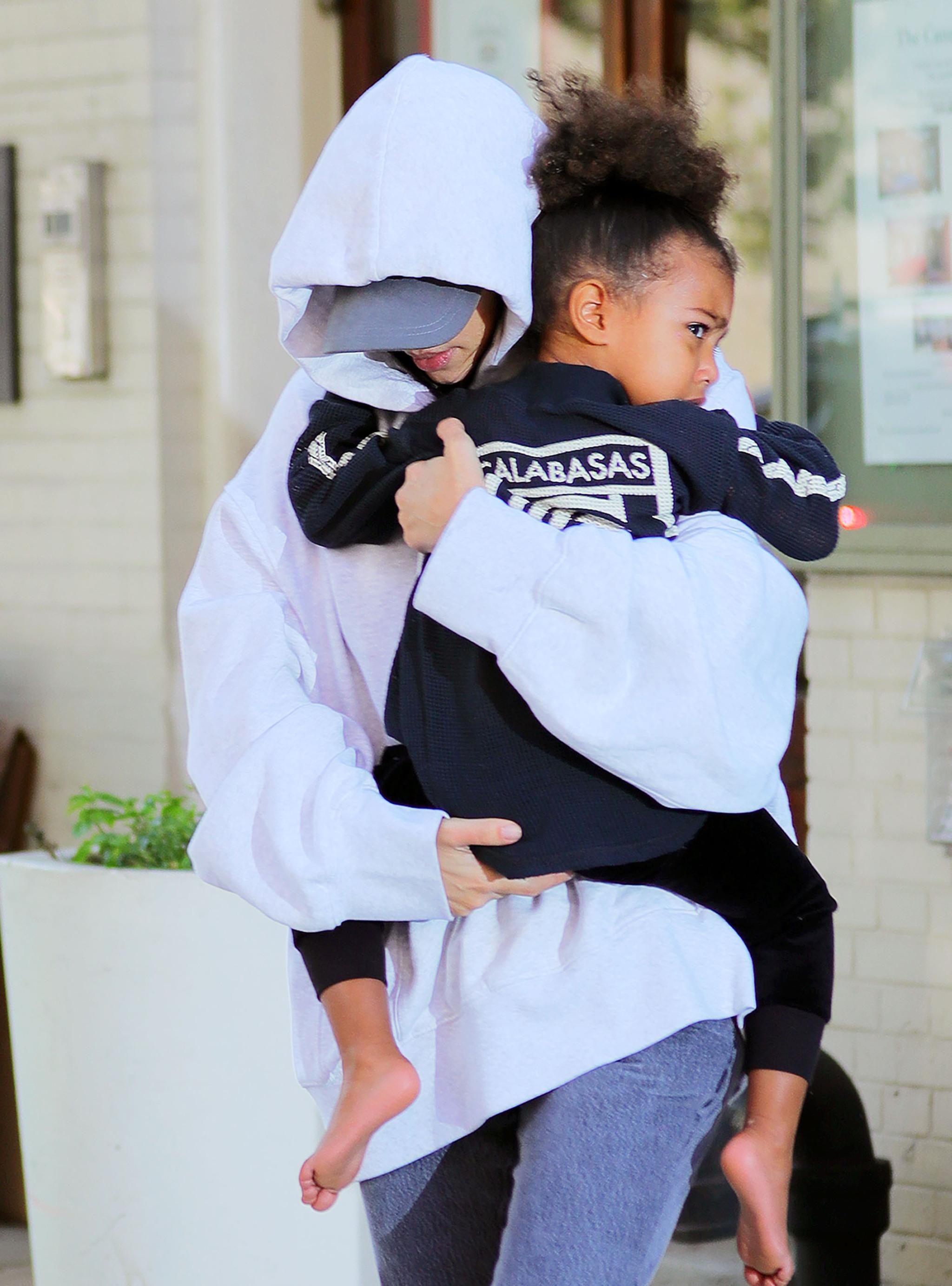 Kim, completamente cubierta por una gran sudadera, lleva en brazos a...