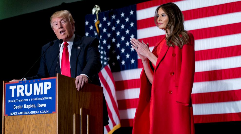 Melania Trump junto a su marido, con un abrigo rojo sobre los hombros