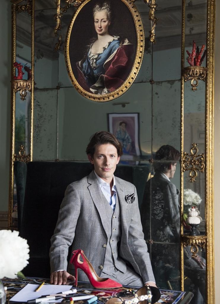 Con un traje Príncipe de Gales en su mesa  de trabajo, una joya  de...