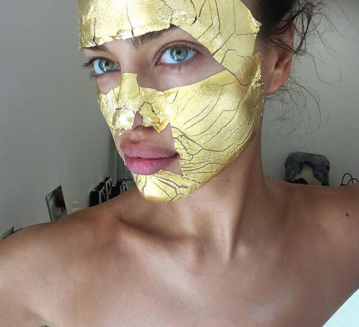 Irina Shayk  luciendo una mascarilla dorada de Mimi Luzon.