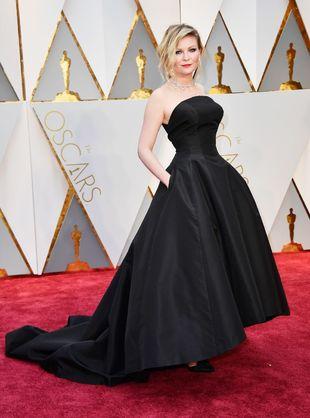 La actriz Kirsten Dunst con vestido negro de Dior y joyas de Chopard.