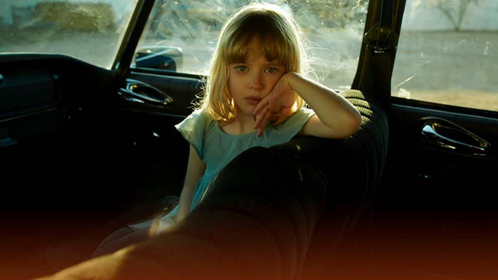 Niña aburrida dentro de un coche.