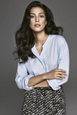Sassa, con camisa azul y falda de tweed y pendientes, todo de DIOR.