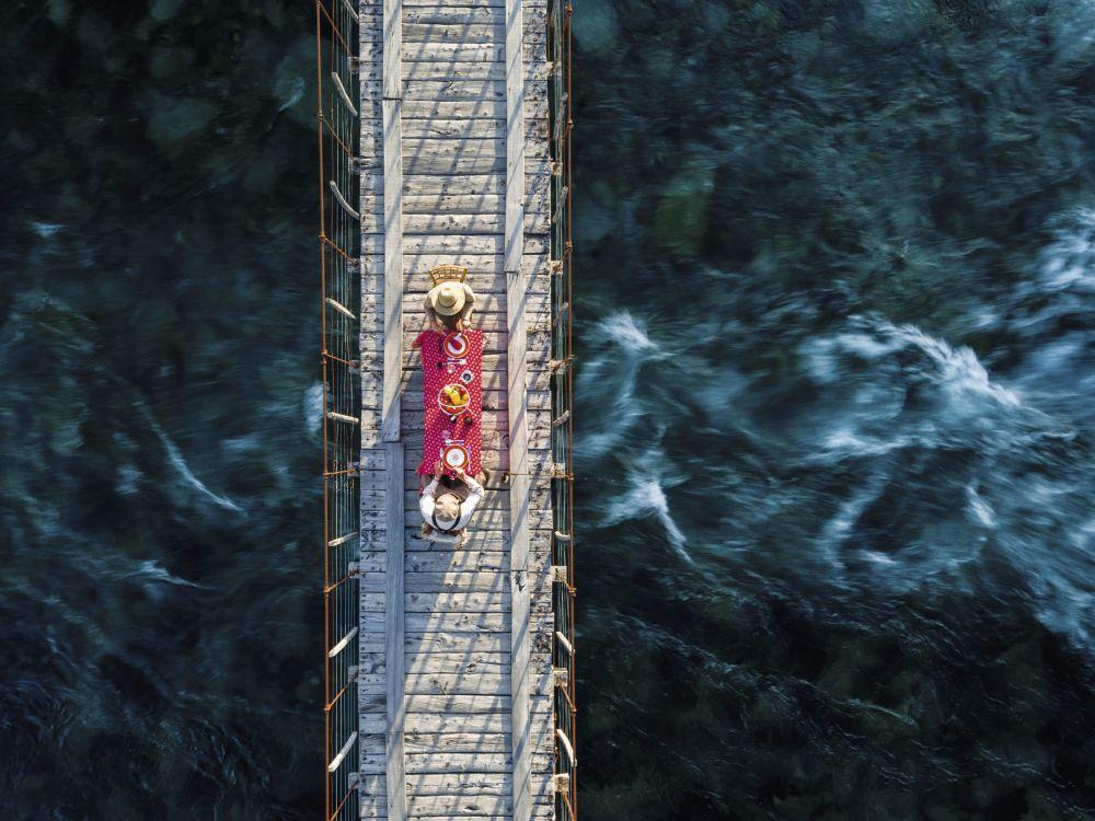 Comer en un puente colgante sobre el río Traful.