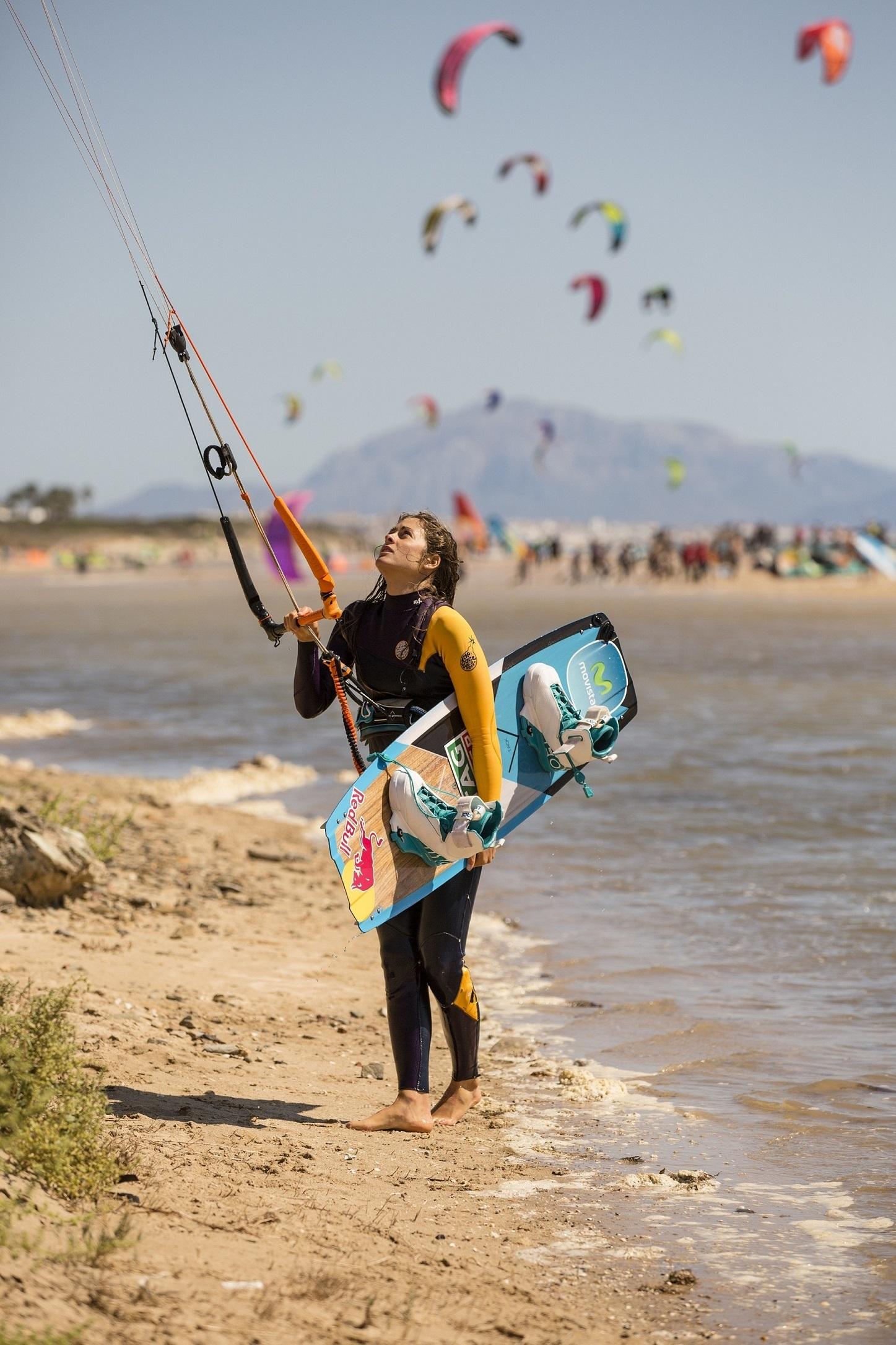 Gisela Pulido con su cometa por la orilla.