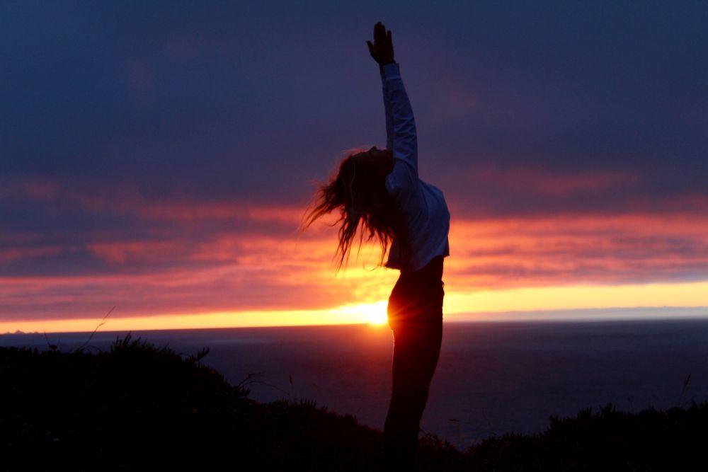 Nuestra yogui practicando yoga durante una puesta de sol