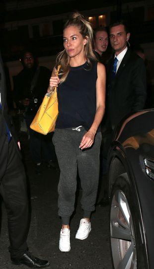 Sienna Miller con un look deportivo compuesto por básica, pantalones...