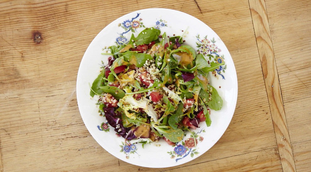 Ensalada gourmet con hojas verdes y brotes.