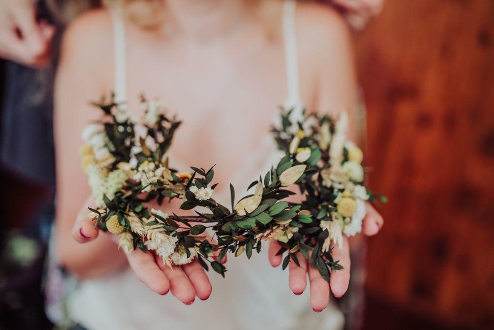 La corona floral doble a base de tonos verdes, amarillos y blancos era...