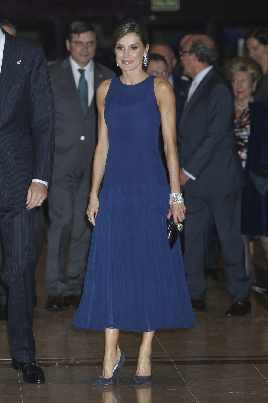La reina Letizia con vestido azul oscuro y falda plisada de Felipe...