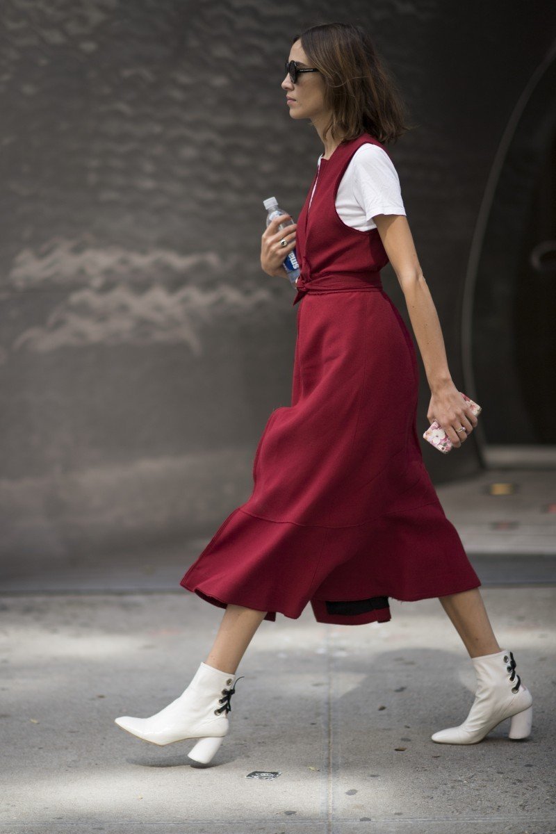 Alexa Chung combina botines blancos con vestido midi.