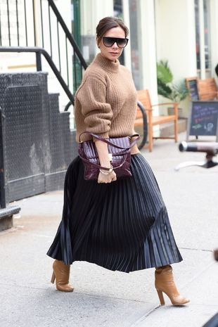 Victoria combinando las botas con una falda midi y suéter camel.