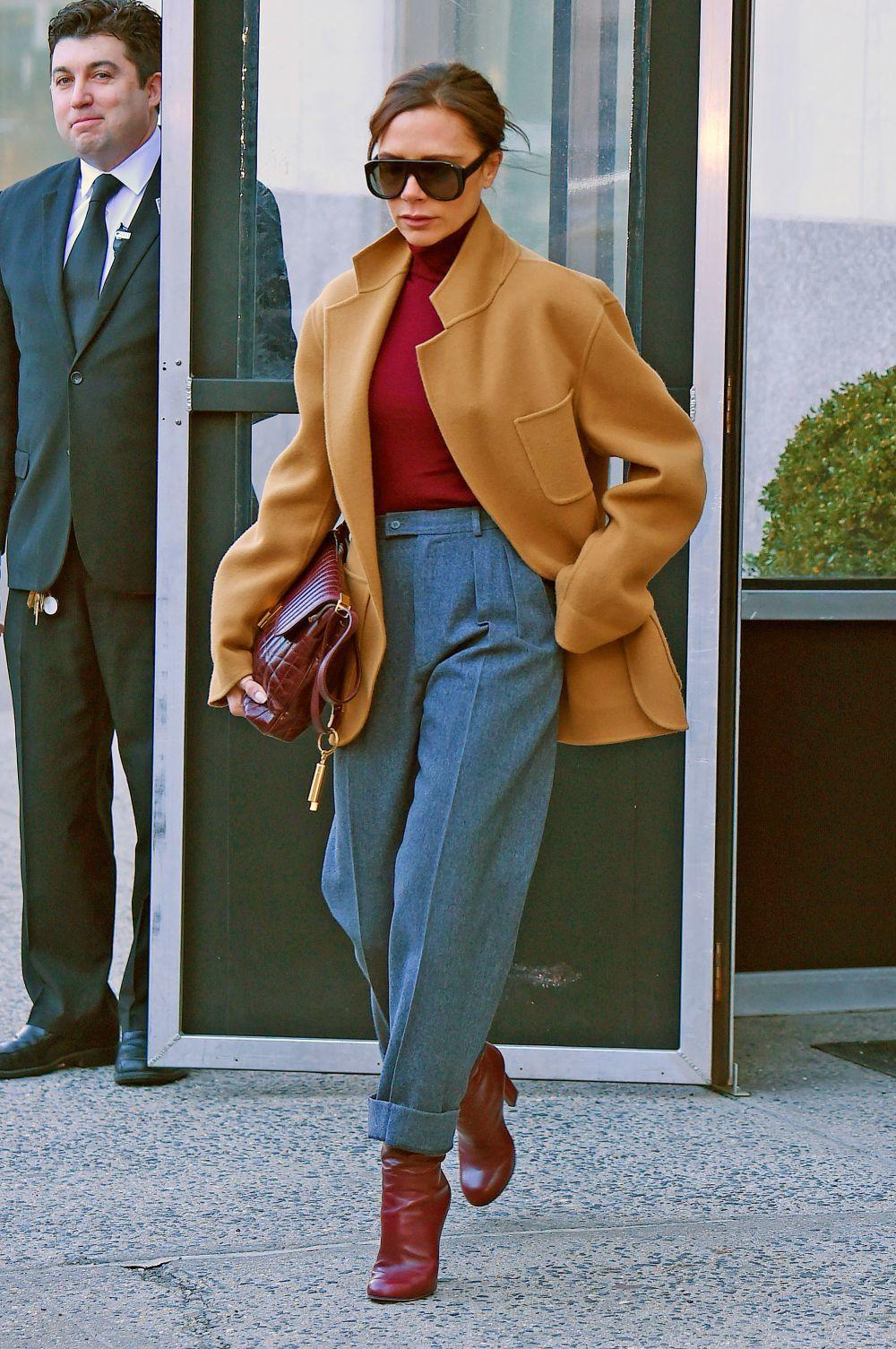 Con pantalones subidos y botas combinadas en color con el suéter.