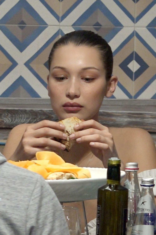 Bella Hadid comiendo un sandwich.