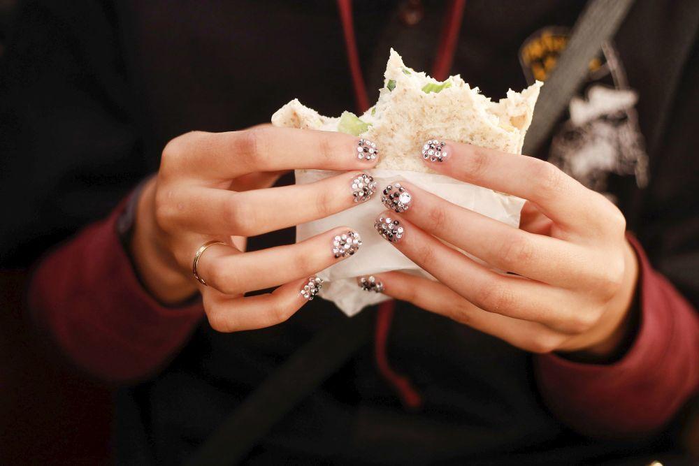 Chica comiendo sanwich con uñas pintadas.