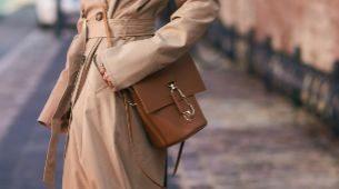 Look clásico de trench nude y bolso de cuero marrón.