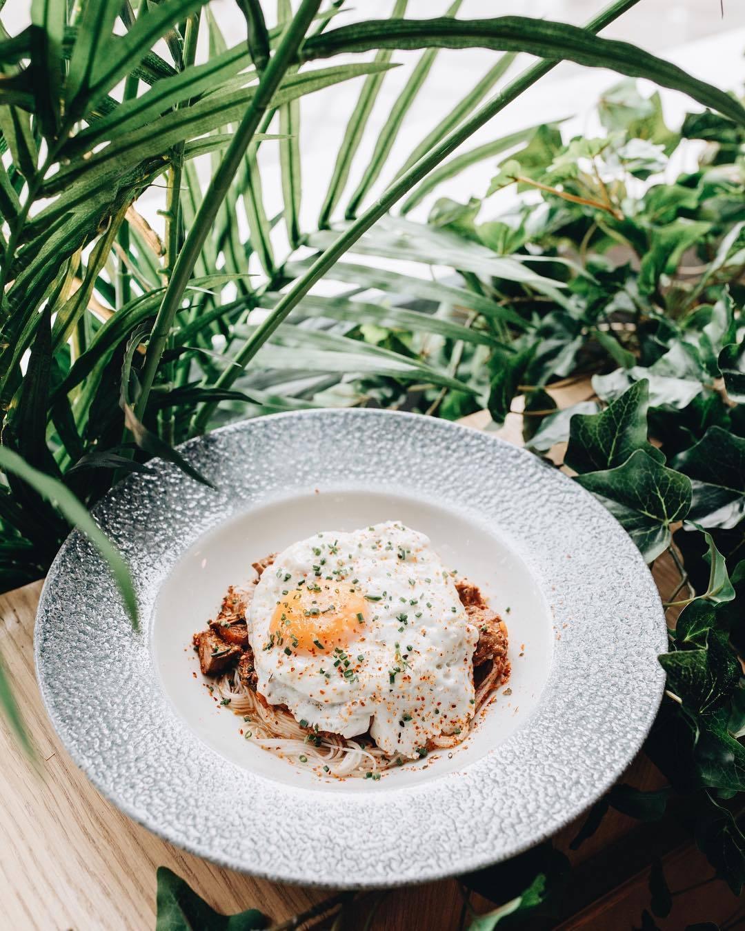 Pasta fina de arroz con ragú de ternera y huevo frito en Restaurante...