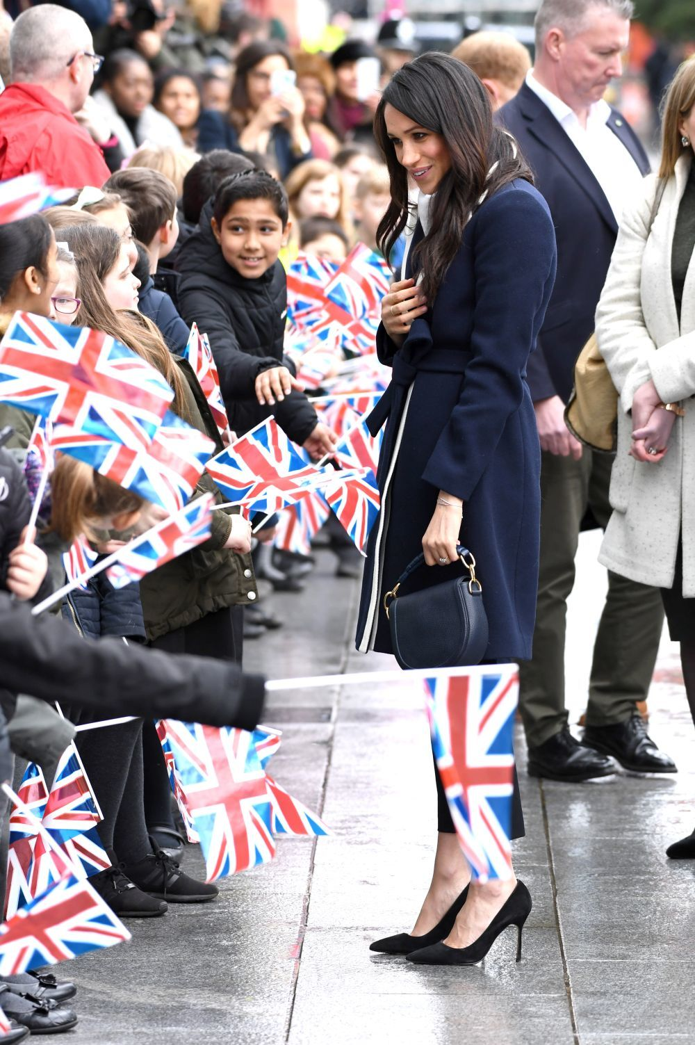 Meghan Markle en un acto público, con banderas de Reino Unido.