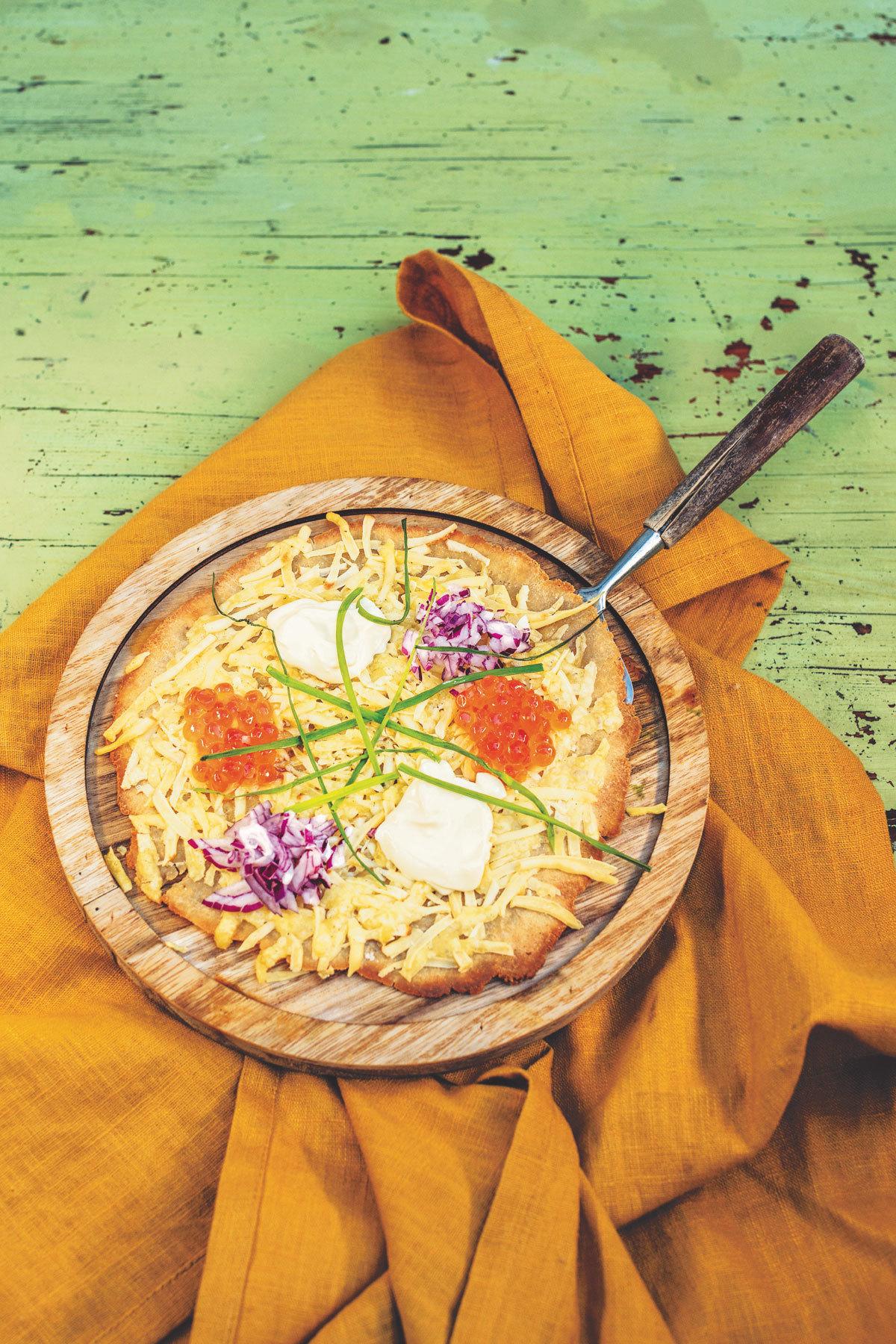 Pizza de huevas de salmón, cebolla morada y crème fraîche