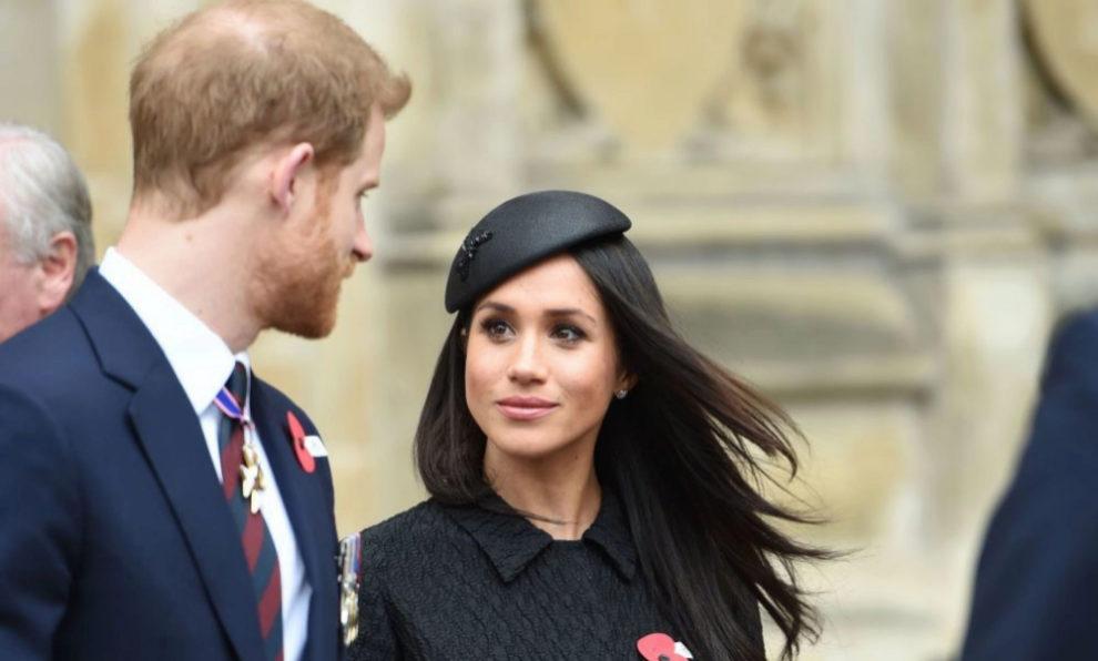 Meghan Markle con biona y traje negro junto al príncipe Harry.