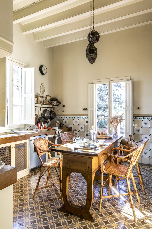 En el centro de la cocina, la mesa de madera con sillas de mimbre...