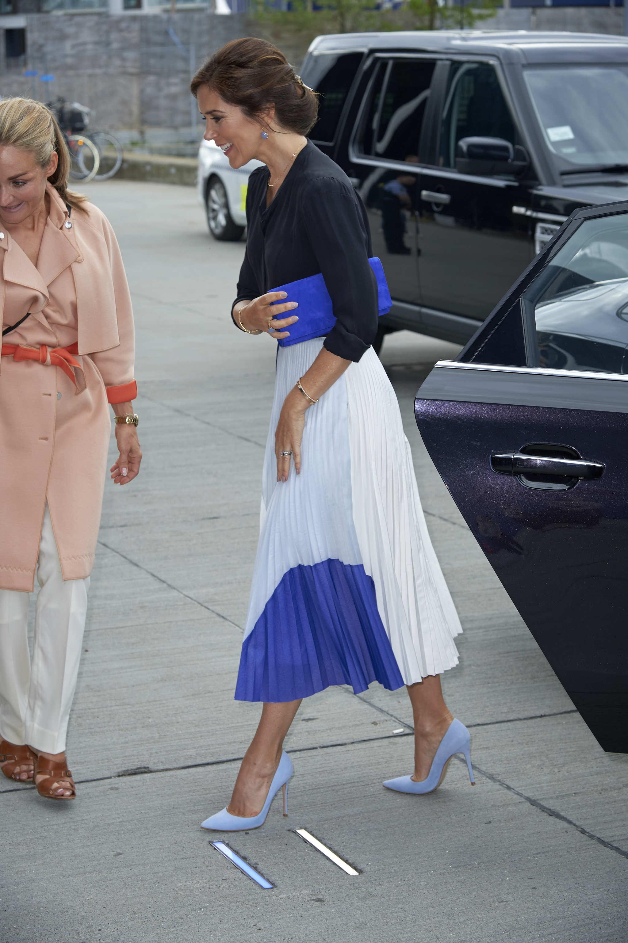 Mary de Dinamarca con una falda plisada en tonos claros, combinada con...