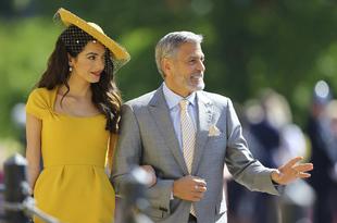 Amal Clooney, con vestido mostaza de Stella McCartney, junto a George...