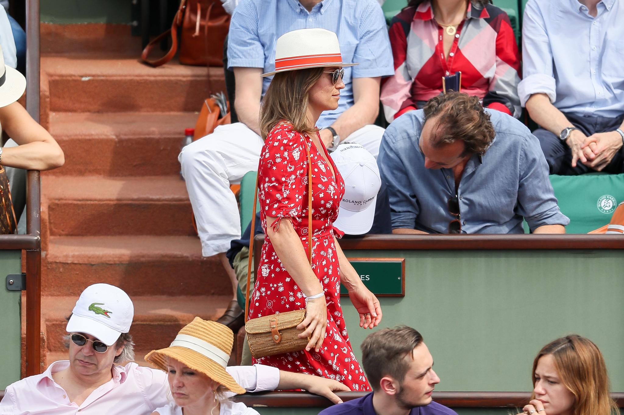 Pippa combina el vestido wrap, con un bolso de mimbre, un sombrero...