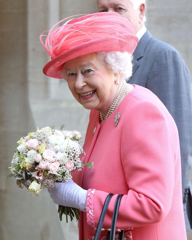 La Reina Isabel II con ramo de flores y traje rosa de chaqueta.