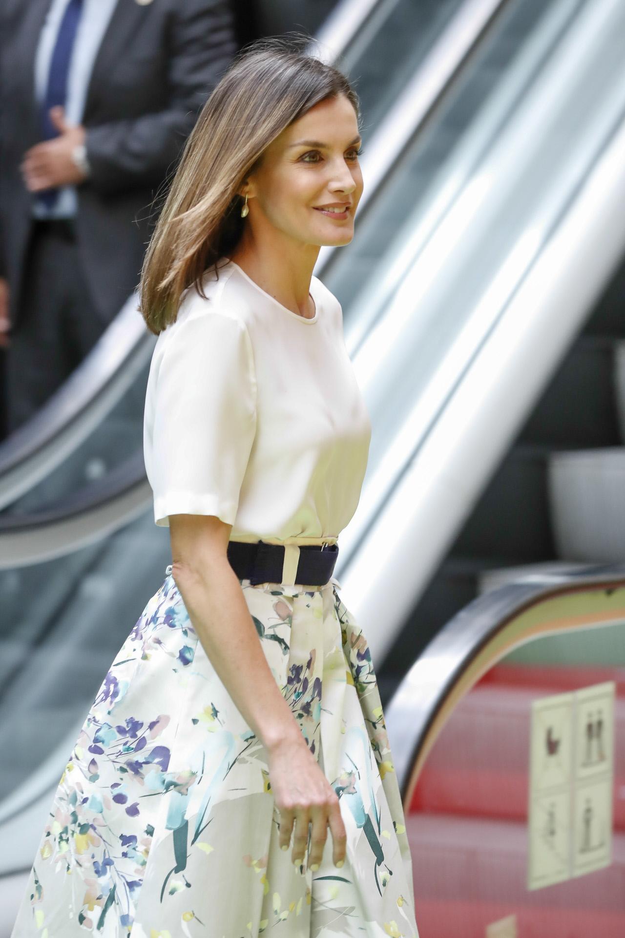 La reina Letizia con falda de flores, blusa blanca y cinturón.