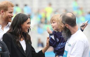 Meghan Markle y el príncipe Harry con una pequeña fan.