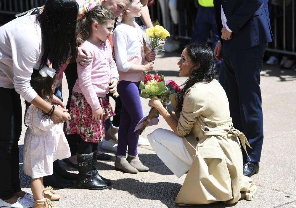 Meghan Markle recibiendo un ramo de flores.
