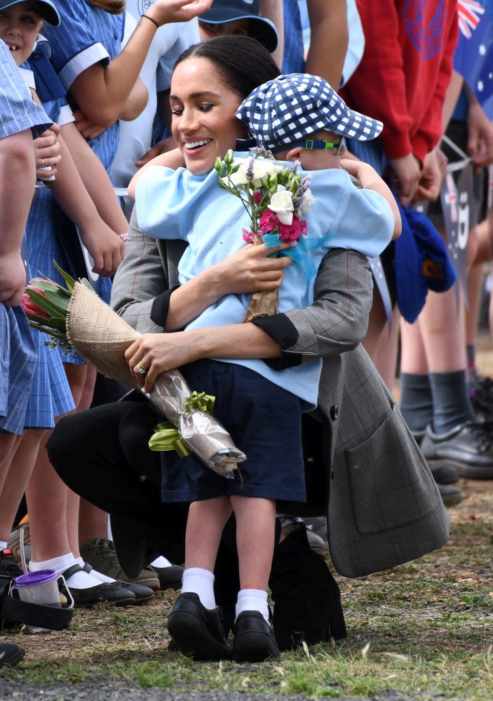 Meghan Markle abraza a un niño en uno de los actos de su gira por...