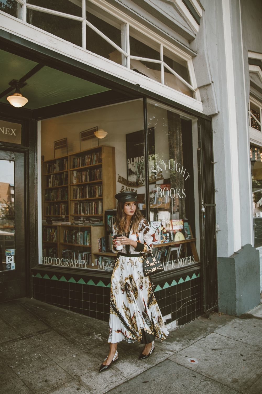 Alexandra Pereira, vistiendo blusa estampada, falda plisada y bolso....