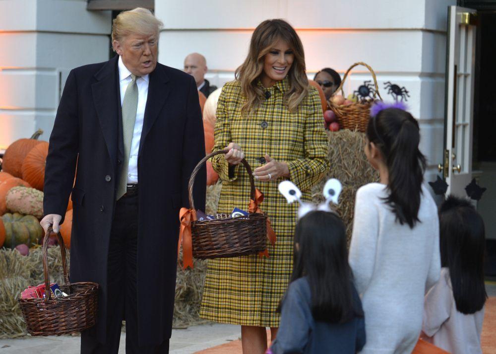 Donald Trump y Melania Trump repartiendo caramelos a los niños.