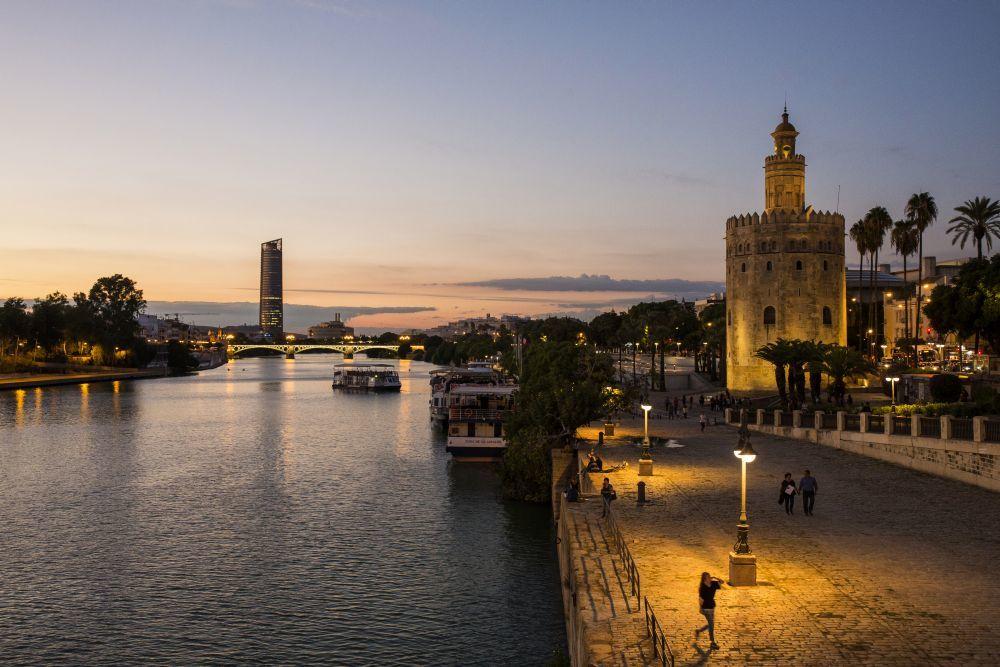 Sevilla al anochecer, con la Torre del Oro iluminada y el Puente de...