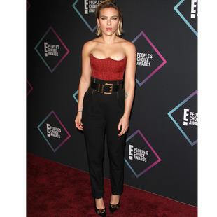 Con corsé rojo y negro y pantalones negros, de Versace.