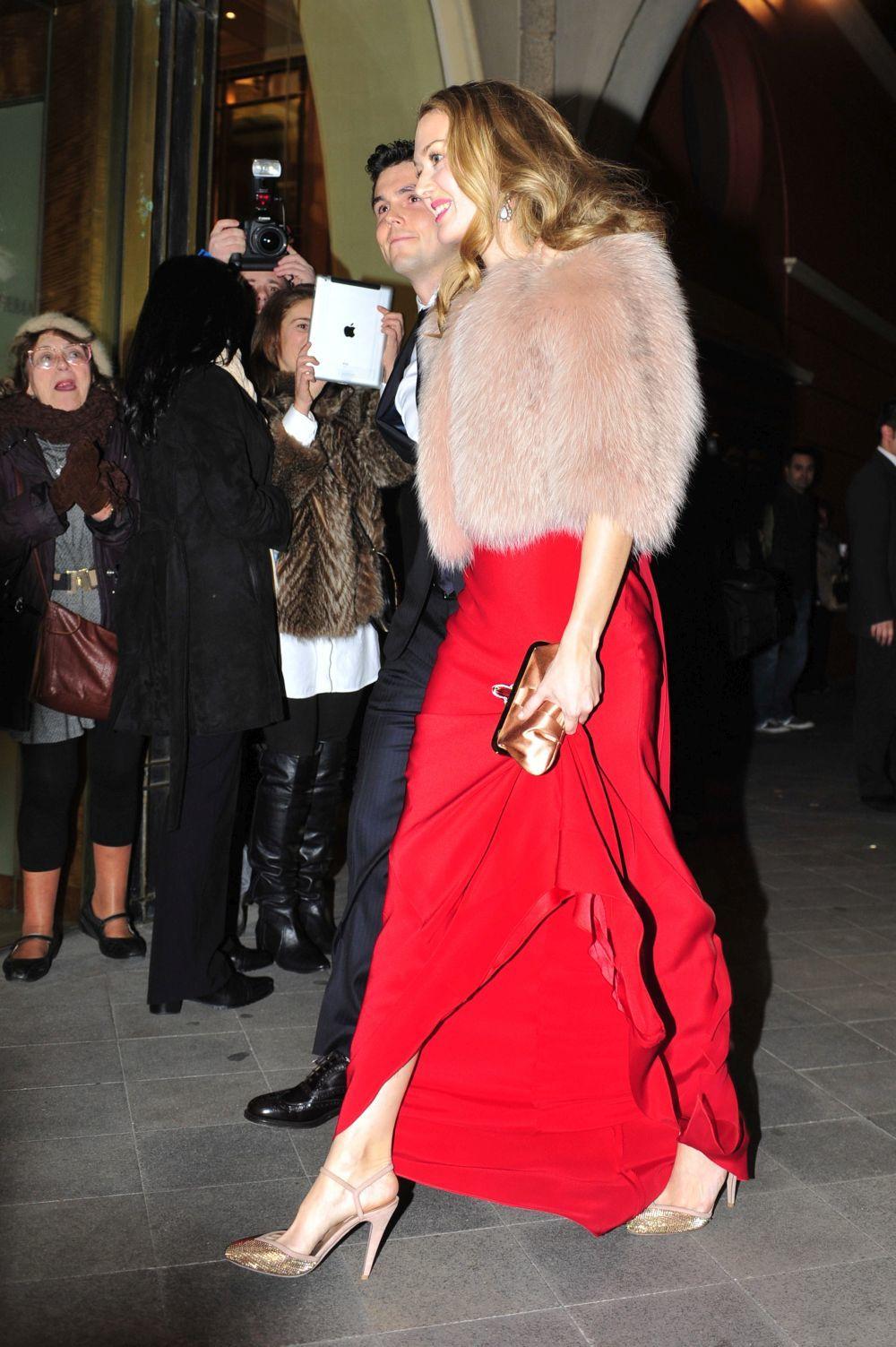 Con vestido rojo y estola de piel.