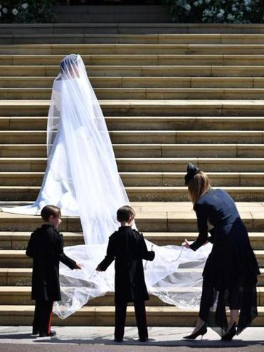 Durante la boda, Clare Waight Keller colocando el vestido a Meghan...