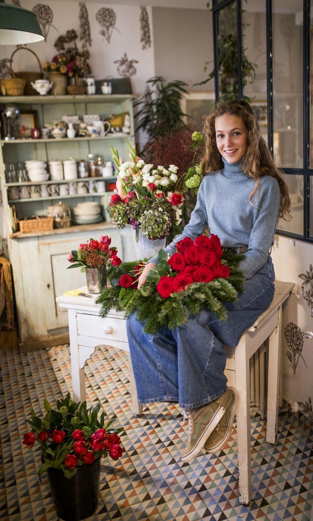 Angélica en la cocina de su casa, con los arreglos de flores de su...