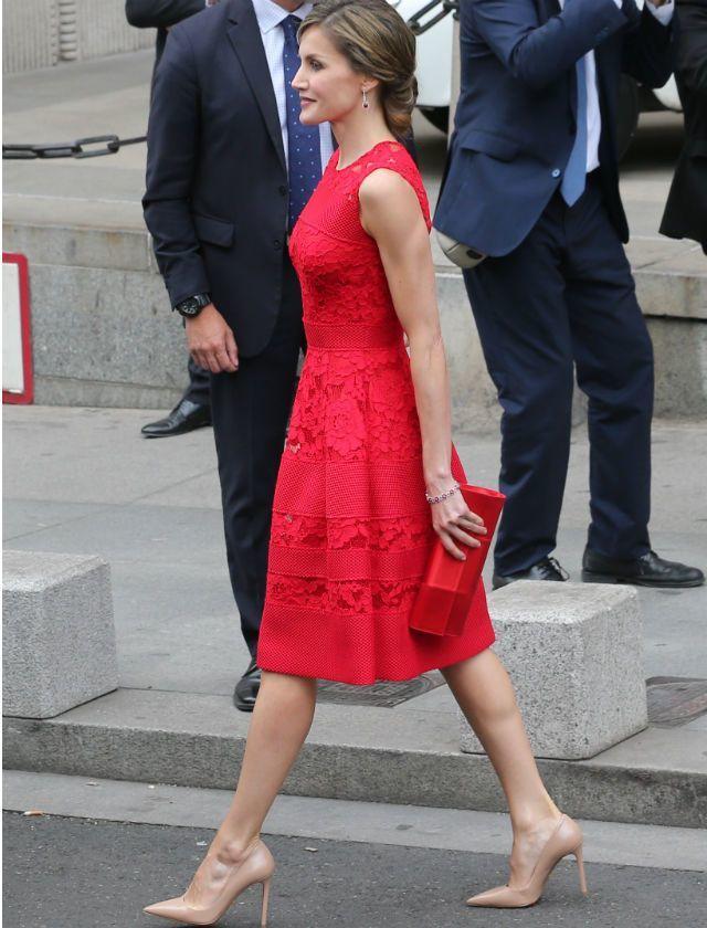La Reina con vestido rojo y salones nude.