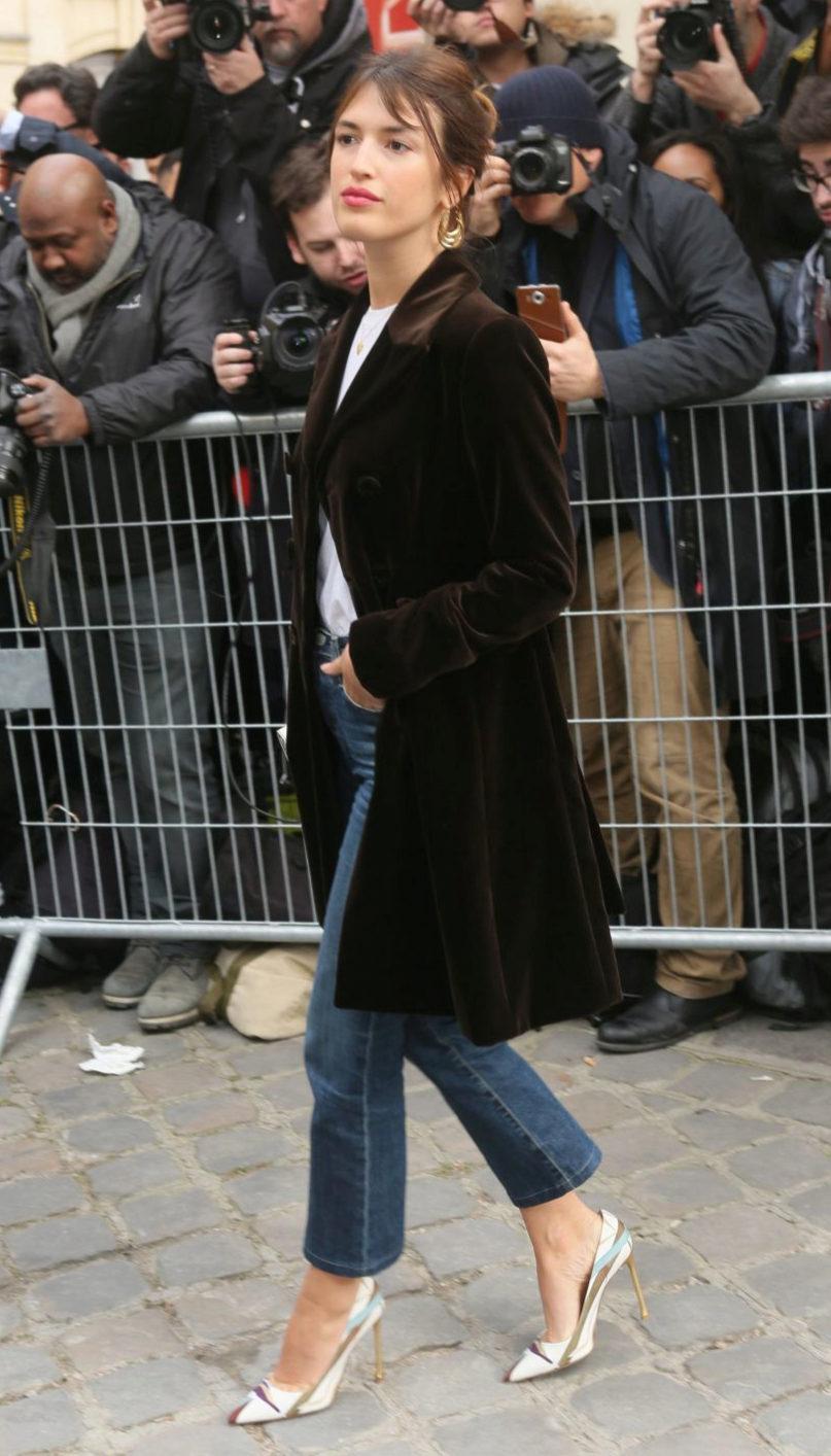 Jeanne Damas combina su abrigo de terciopelo con jeans y salones.