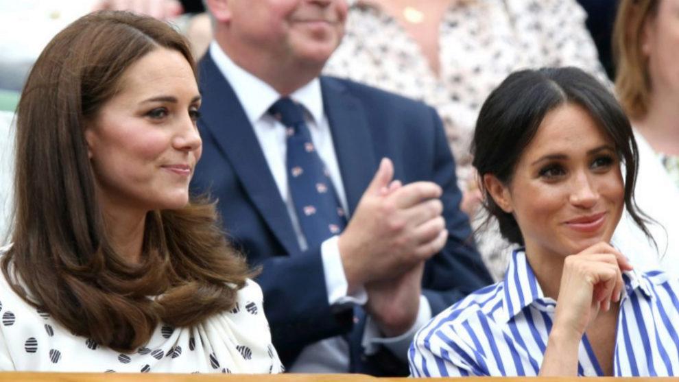 Kate Middleton y Meghan Markle sentadas en un partido de tenis.