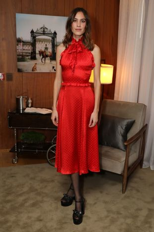 Alexa Chung con un vestido midi rojo en satén.