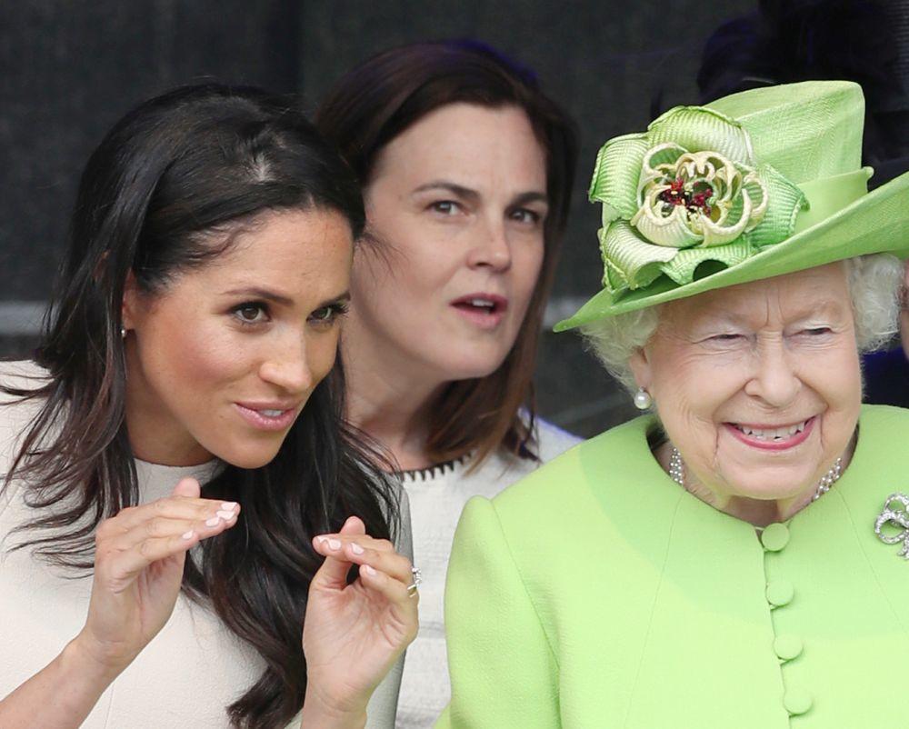Samantha Cohen sentada detrás de Meghan Markle e Isabel II.