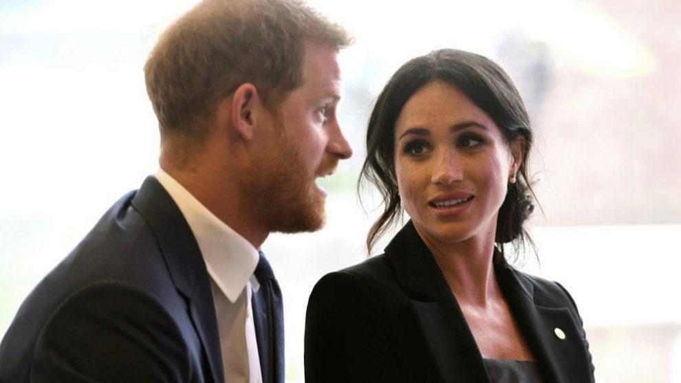Meghan Markle y el príncipe Harry sentados y hablando en un acto.