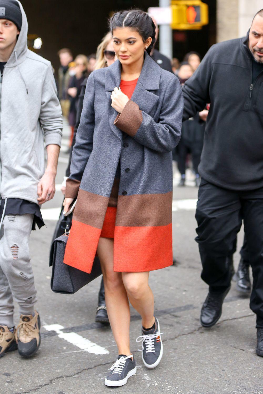 Kylie Jenner con un abrigo gris y naranja de Hugo Boss y falda a...
