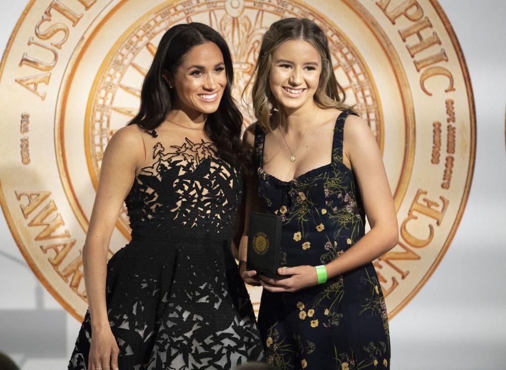 Meghan Markle junto a una joven en una gala durante su gira por...