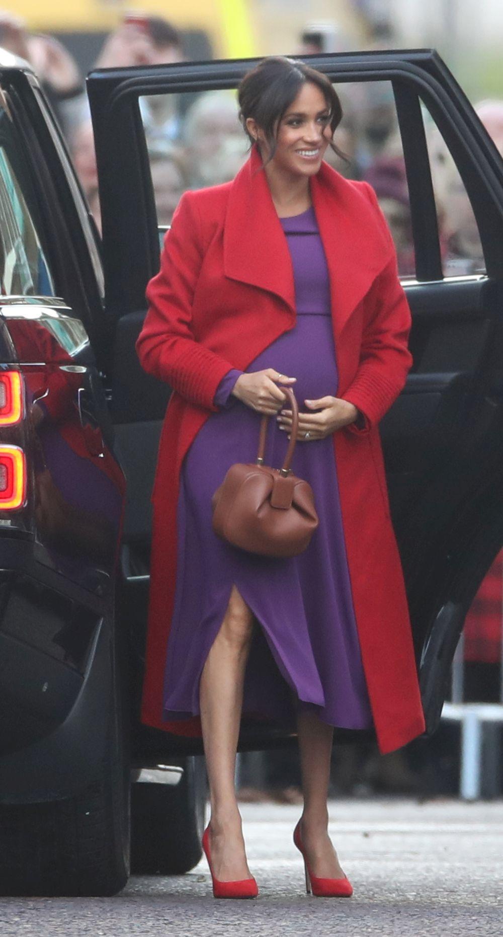 Meghan Markle con un abrigo rojo y un vestido morado en su